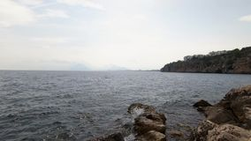 Beautiful landscape view of the cloudy sky and the sea, small waves beating against the rocks stock footage