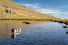 Beautiful landscape view of Greendale Tarn in the Lake District. National Park, UK. A man relaxing and enjoying refreshing bath in cold tarn water on a royalty free stock photography