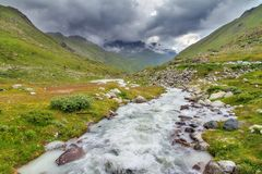 Moiry river in the valley. Beautiful landscape view of the Moiry glacier river of melted ice down the valley with a ominous sky with clouds in summer in the stock photography
