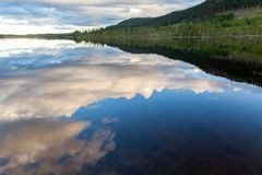 Beautiful landscape view of mountains, forest and cloudy sky reflection in calm water. Horizontal composition Stock Photos