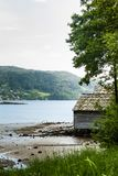 Old norwegian cottage by lake and forest Stock Photography