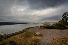 Beautiful landscape view of a picnic resting area by the water with dark dramatic cloudscape. stock photo