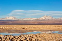 Vacation in chile. Beautiful landscape view of salty tebinquiche lagoon in atacama desert, chile with andes mountains in the background and lenticular clouds in Stock Images