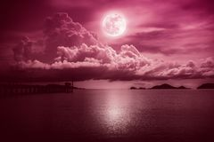 Beautiful landscape view of the sea. Colorful red sky with clouds and bright full moon on seascape to night. Serenity nature royalty free stock photography