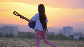 Beautiful landscape view at sunset. funny little girl musician playing the guitar walks outdoors dandelions field away from town b