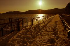 Beautiful landscape view in twilight time of walkway or footpath beside street road covered with white snow in winter seasonal. stock photo