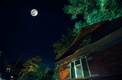 Beautiful landscape village street with buildings and trees and big full moon at the night sky. Big Caucasus . Royalty Free Stock Photos