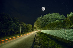 Beautiful landscape village street with buildings and trees and big full moon at the night sky. Big Caucasus . Stock Photography