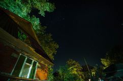 Beautiful landscape village street with buildings and trees and big full moon at the night sky. Big Caucasus . Royalty Free Stock Photography