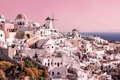 Beautiful landscape with white buildings and vintage windmills in Oia on Santorini island, Greece at sunset stock photography