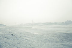 A beautiful landscape with a white, snowy road with safety poles in the winter Stock Images