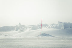 A beautiful landscape with a white, snowy road with safety poles in the winter Royalty Free Stock Photos