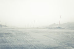 A beautiful landscape with a white, snowy road with safety poles in the winter Royalty Free Stock Photo