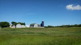Wisconsin Farm Scene in Kenosha County. A beautiful landscape of a Wisconsin farm scene, with multiple blue barns located in Kenosha county. Big open field or royalty free stock photography