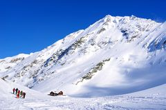 Beautiful landscape with wooden chalet, blue sky and sunshine in winter. Fagaras Mountains Royalty Free Stock Image