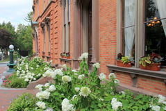Beautiful landscaped garden outside famous Canfield Museum,Saratoga,New York,2015. Beautifully landscaped garden and window boxes with seasonal flowers serve as Royalty Free Stock Photography