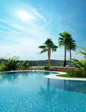 Beautiful landscaped tropical swimming pool. Beautiful landscaped tropical turquoise blue swimming pool with a curving wall leading to palm trees under a sunny Royalty Free Stock Photo