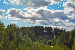 White clouds float above a green forest. Beautiful landscapes are found in the countryside stock images