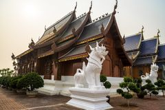Beautiful Lanna style wooden building with white singha statues at a Buddhist temple in Thailand. royalty free stock photos