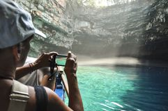 Tourist is taking photo of underground crystal cave lake. stock images