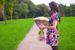 Beautiful large bouquet white roses at the hands of a young girl in colored dress Royalty Free Stock Image