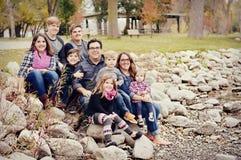Beautiful large family sitting on rocks Royalty Free Stock Images