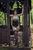 Beautiful large full brunette girl in sexy black lingerie, stockings and corsage in old ruins metal decorated public buildings. Royalty Free Stock Photo