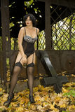 Beautiful large full brunette girl in sexy black lingerie, stockings and corsage in old ruins metal decorated public buildings. Stock Photos