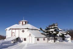 Beautiful large octogonal white barn with red trimmed windows and doors. Seen during a sunny winter day, Saint-Antoine-de-Tilly, Quebec, Canada royalty free stock photography