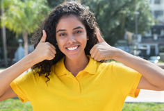 Beautiful latin american girl with long dark hair showing both thumbs Royalty Free Stock Image