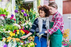 Beautiful woman buying freesias at the advice of a helpful vendo. Beautiful Latin American women buying freesias at the advice of a helpful and handsome vendor Royalty Free Stock Images
