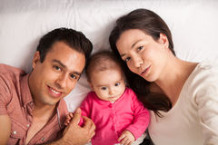 Beautiful Latin family lying on a bed Stock Photo