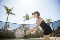 Concentrating on her serve. Beautiful latin female tennis player training on the tennis court, racket and ball in had about to make a serve Royalty Free Stock Image