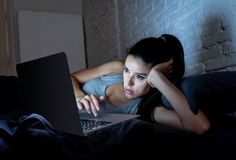 Pretty latin woman bored and addicted to her device in bed. Beautiful latin internet addicted woman working and surfing on her computer bored, sleepless and stock images