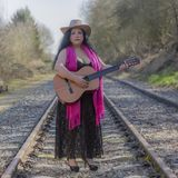 Beautiful latin woman with black dress playing the guitar on the train tracks. With a pink shawl, a brown hat and a guitar on an autumn day with blurred royalty free stock image