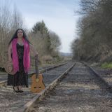 Beautiful latin woman with black dress standing on the train tracks with a pink shawl. A brown hat and a guitar on an autumn day with blurred background stock image