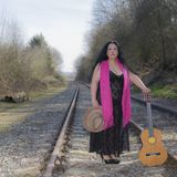 Beautiful latin woman with black dress standing on the train tracks. With a pink shawl, a brown hat and a guitar on an autumn day with blurred background stock photos