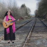 Beautiful latin woman with black transparent dress playing the guitar on the train tracks with a pink shawl, a brown hat and a gui. Tar on an autumn day with royalty free stock image
