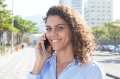 Beautiful latin woman with blue blouse at phone in the city Royalty Free Stock Photos