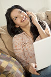 Beautiful Latin Woman on Cell Phone & Laptop. A stunningly beautiful young Latin Hispanic woman sitting on a settee having fun on her laptop and laughing while Royalty Free Stock Photo