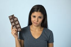Beautiful latin woman with chocolate bar feeling guilty after biting  on blue background in sugar and sweet abuse. Young beautiful latin woman with chocolate bar Royalty Free Stock Photography