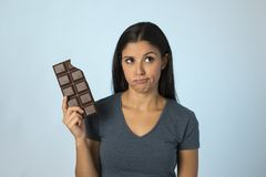 Beautiful latin woman with chocolate bar feeling guilty after biting  on blue background in sugar and sweet abuse. Young beautiful latin woman with chocolate bar Stock Image