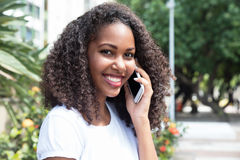 Beautiful latin woman with curly hair at phone in a park Royalty Free Stock Image