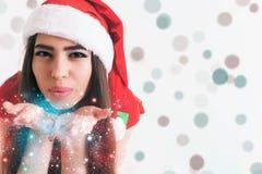 Beautiful latin woman fairy blowing magical glitter at christmas day. Stock Photo