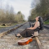 Beautiful latin woman with long black hair, wearing a black transparent dress sitting on the train track looking upwards. Next to a hat and a guitar in south royalty free stock photos