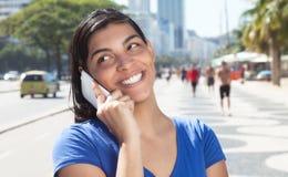 Beautiful latin woman with long dark hair at phone in city Stock Image