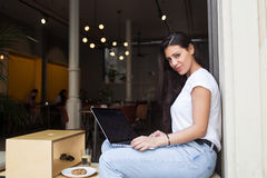 Beautiful latin woman posing for the camera while working on her laptop computer during breakfast. Charming female freelancer using net-book for remote job while Stock Photography