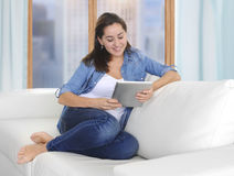 Beautiful Latin woman sitting on living room sofa couch at home enjoying using digital tablet computer Stock Image