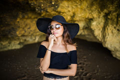 Beautiful latin woman thinking with hat and sunglasses sunbathing on rocks beach on summer vocation time royalty free stock photos