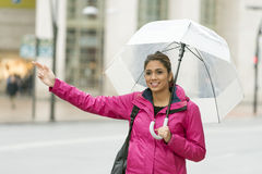 Beautiful latin woman with umbrella hitchhiking in the street. Royalty Free Stock Image